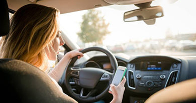young-woman-texting-driving-sunny-day
