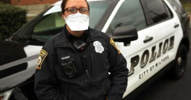 woman-police-mask-stand-by-cruiser